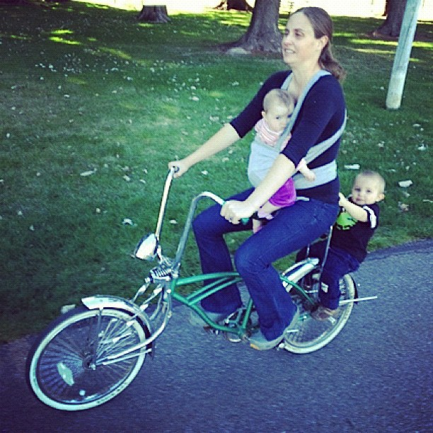 mom carrying two kids on lowrider bicycle baby wearing