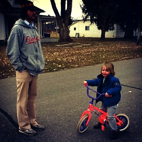 dad teaching crying boy to ride bike