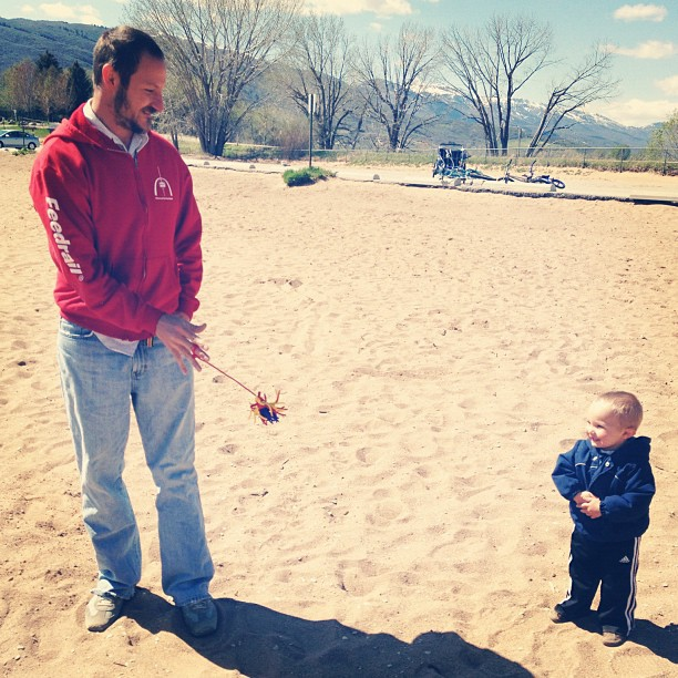 dad and toddler boy playing on beach