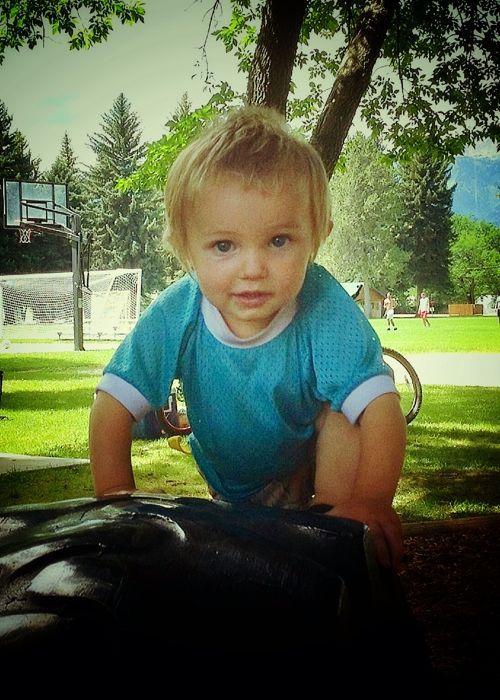little boy on tire in park snapseed