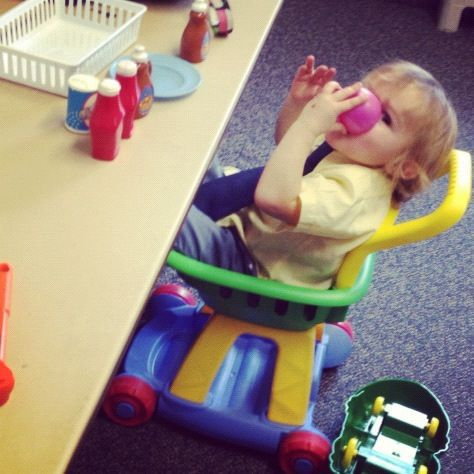 little boy sitting in toy grocery cart instagram