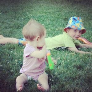 little boy and baby girl lying in grass instagram