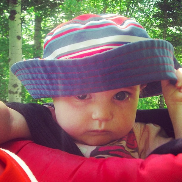 baby girl pulling hat off in baby backpack instagram