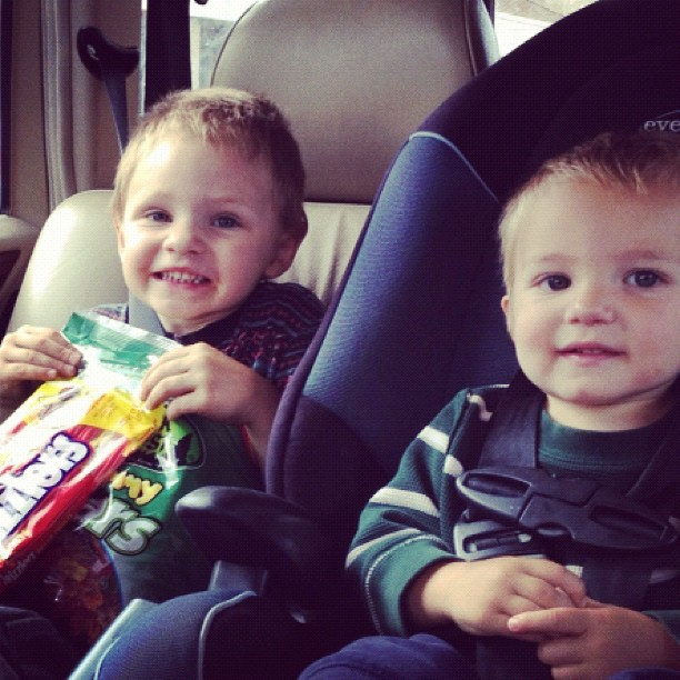 little boy and toddler boy in car seats holding candy instagram