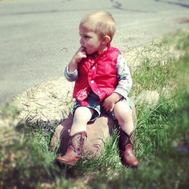 little toddler boy sitting on rock cowboy boots
