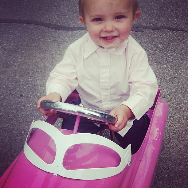 little toddler boy in pink toy car instagram