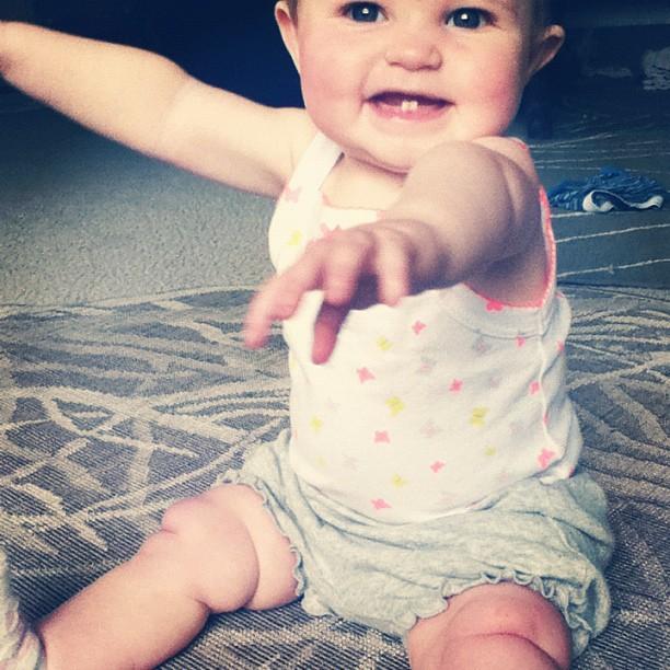 baby girl smiling sitting two teeth
