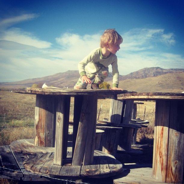 little boy on wooden spool instagram