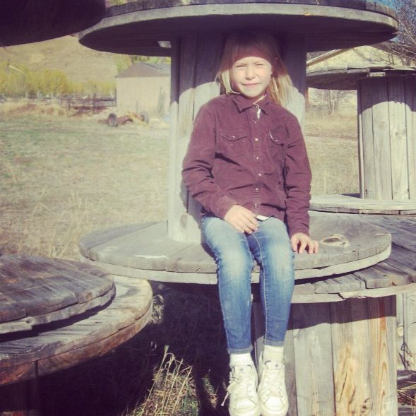 little girl on wooden spool instagram