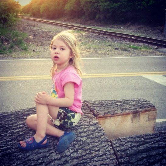 little girl sitting on log near train track instagram