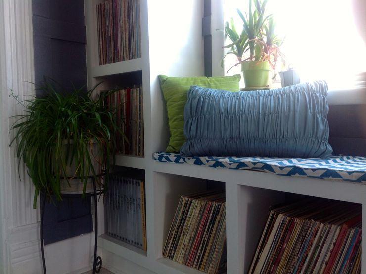 window seat built in bookshelves record collection plants throw pillows