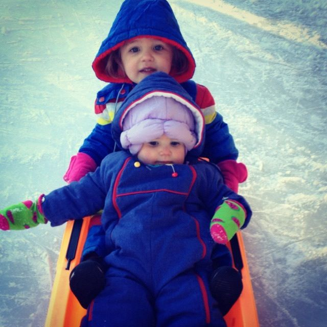 little boy and girl in sled on outdoor ice rink instagram