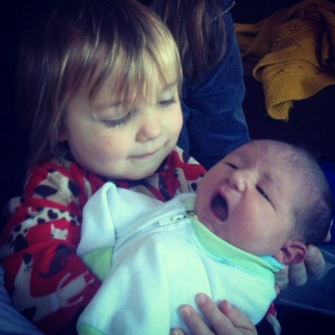 little boy holding newborn brother instagram