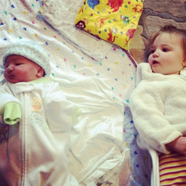 newborn and toddler lying side by side instagram brother sister