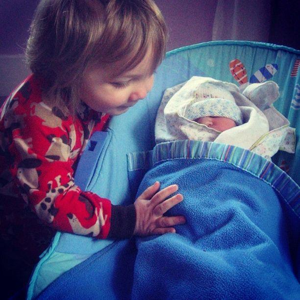 little boy patting newborn brother instagram