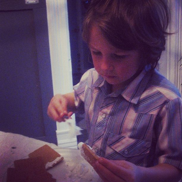 little boy working on graham cracker gingerbread house instagram