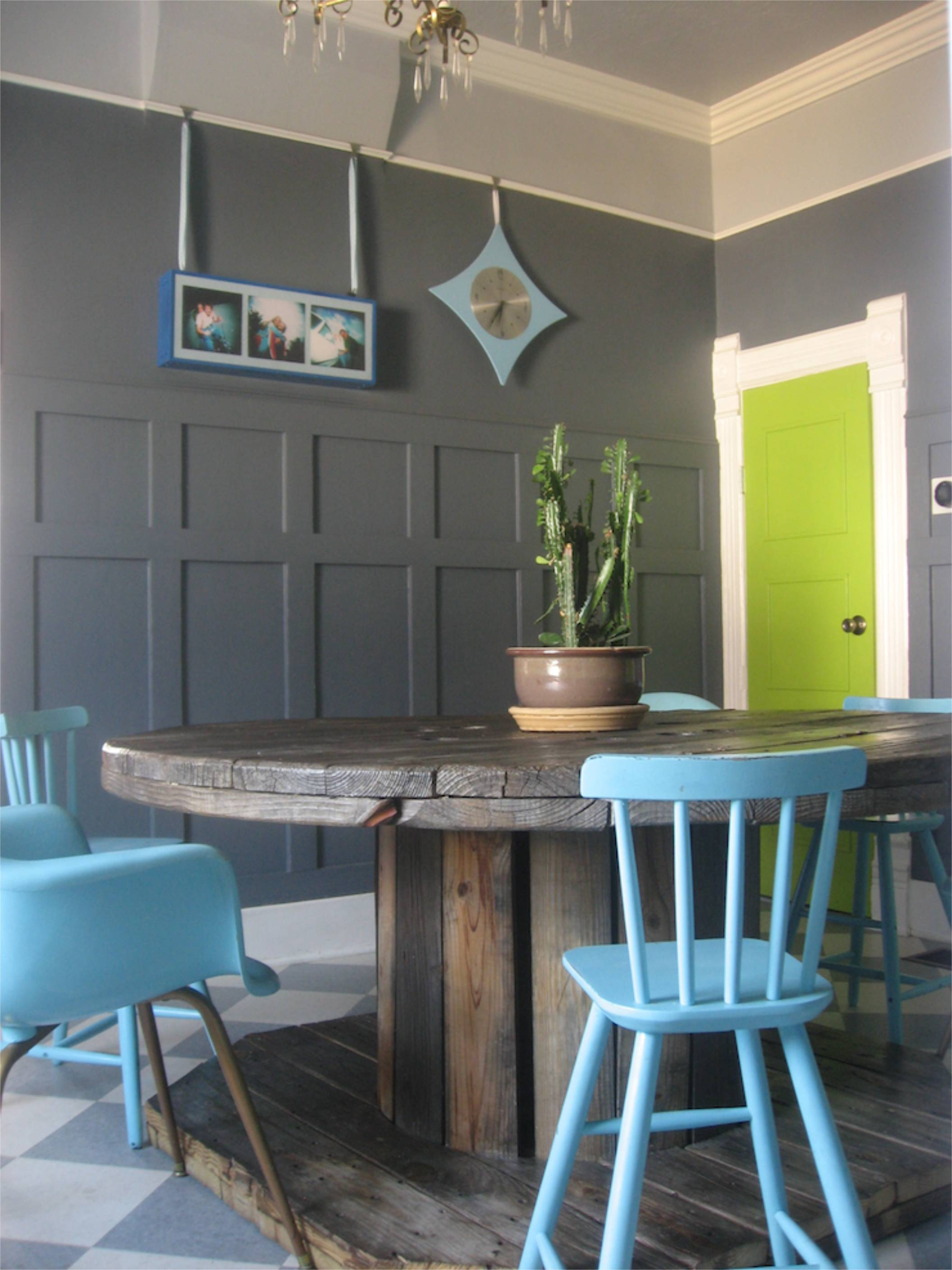 wooden spool dining table grey wainscoting chartreuse door
