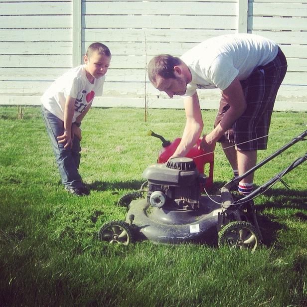 little boy watching dad put gas in lawn mower instagram